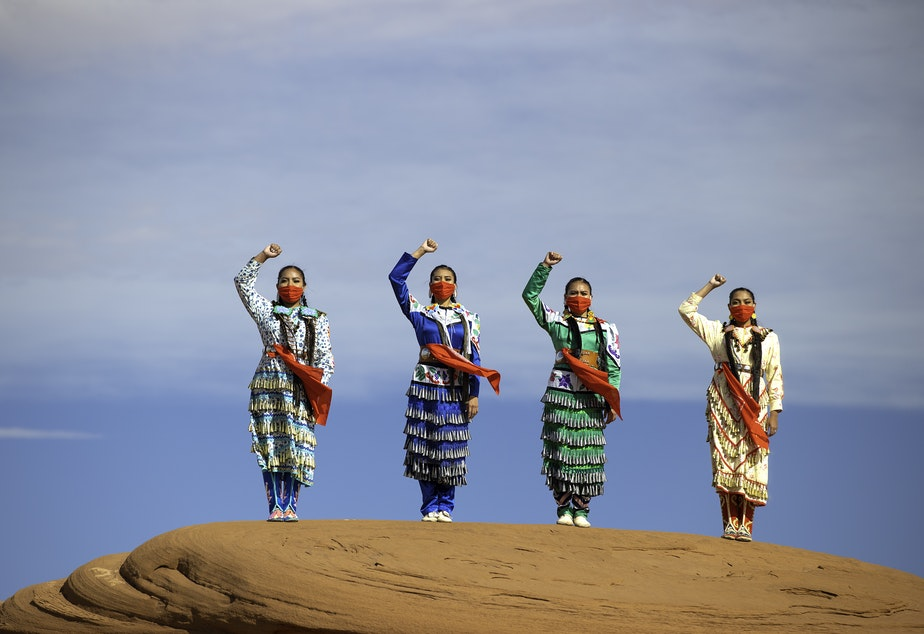caption: Erin and Dion Tapahe and Sunni and JoAnni Begay pose with their fists raised on native land in Monument Valley.