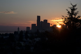 The sun sets behind downtown Seattle.