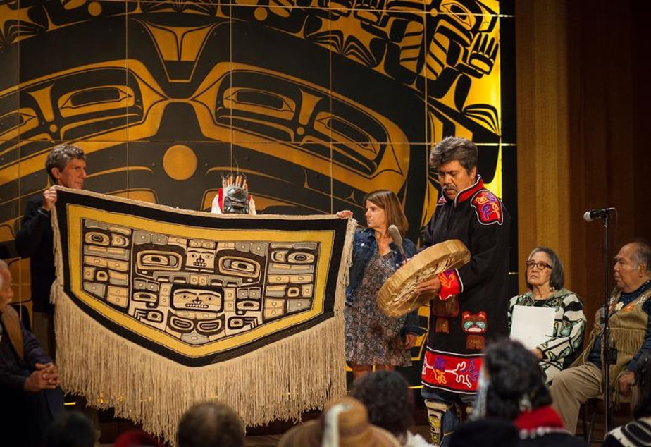 caption: Bruce and Gretchen Jacobsen hold the Chilkat robe they donated to the Sealaska Heritage Institute as Joe Zuboff, Deisheetaan, sings and drums and Brian Katzeek (behind robe) dances during the robe's homecoming ceremony Saturday, August 26, 2017.