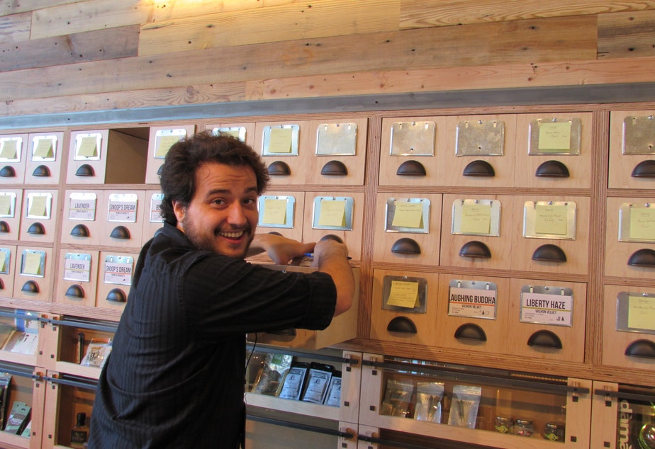 caption: Ben Perez works behind the counter at the new Dockside SODO marijuana retail store.