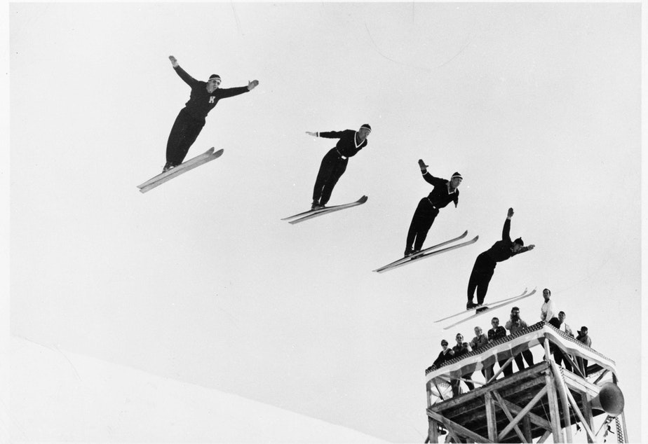caption: Olav Ulland, Gustav Raaum, Alf Engen, and Kjell Stordalen perform a four-person simultaneous ski jump at Sun Valley, Idaho, in December 1948.