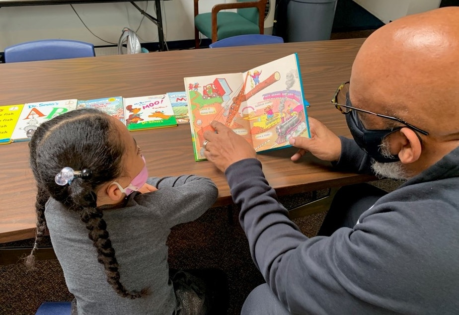 caption: Gerald  Donaldson, a family support worker at Leschi Elementary in Seattle, reads to a kindergartener during the Covid-19 pandemic.