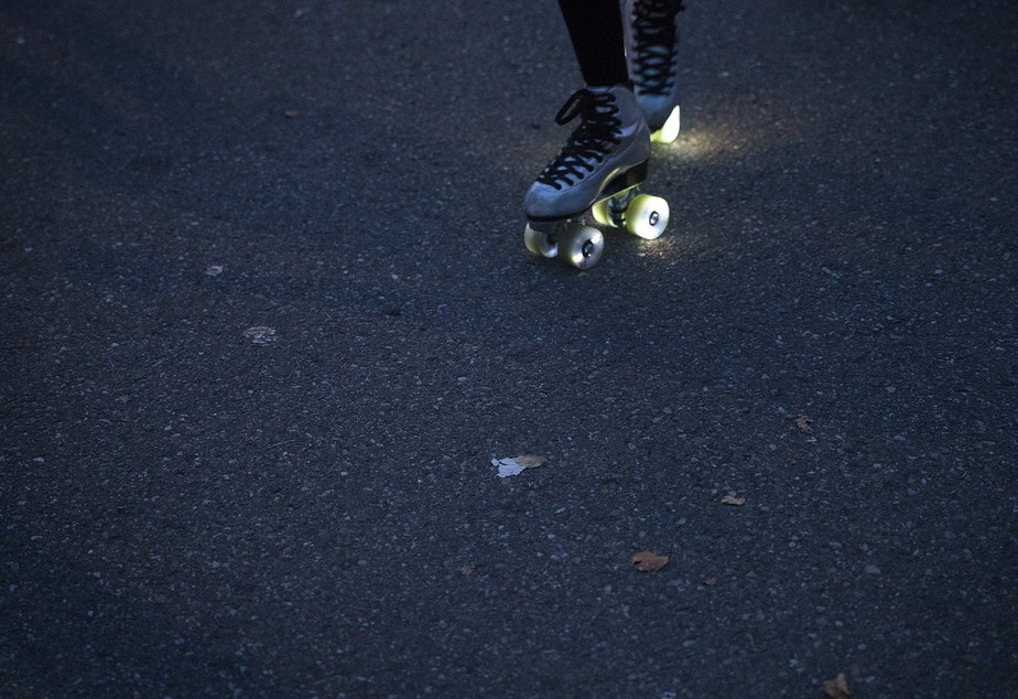 caption: Co-founder of Seattle Skates, Artemis Peacocke, skates with light-up wheels  as the sun goes down on Wednesday, September 30, 2020, along Alki Avenue Southwest in Seattle.