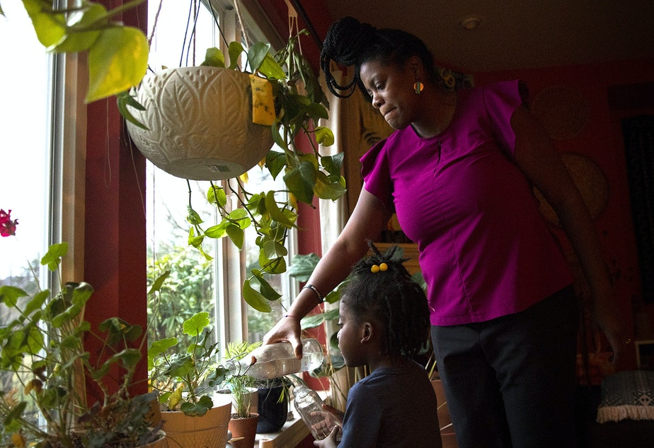 caption: Biggest carbon loser contestant Bernadette 'B' Merikle waters plants with daughter, Julia Merikle, 4, at their home on Wednesday, February 12, 2020, in Snoqualmie.