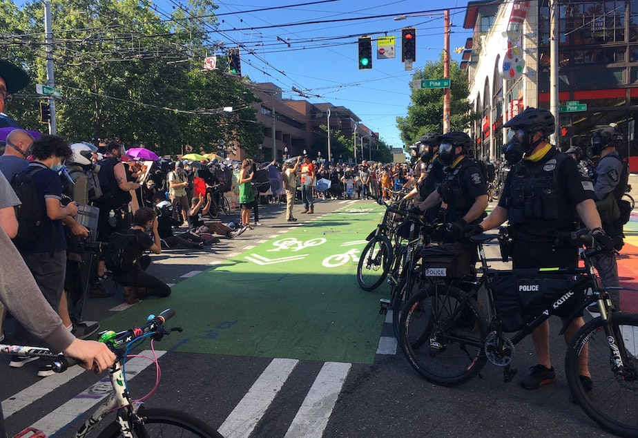 caption: Police officers face off with people protesting onSeattle's Capitol Hill on Saturday, July 25 2020.