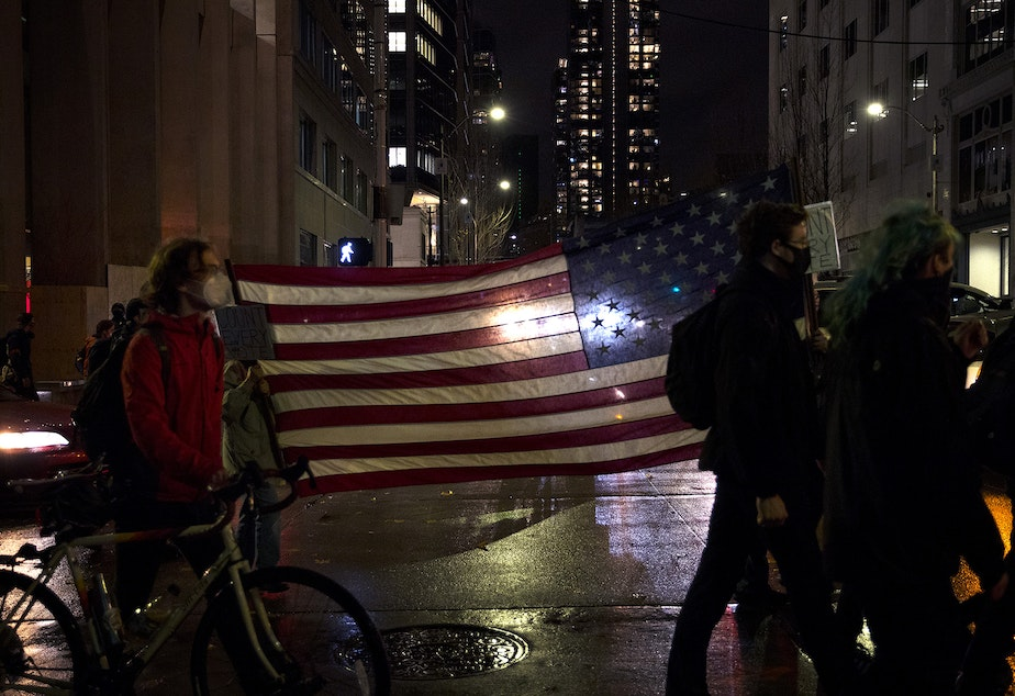 caption: Demonstrators carry an American flag as hundreds marched through Pioneer Square on Wednesday, November 4, 2020, in Seattle. The event was focused on counting every vote and protecting every person. In addition to supporting ongoing vote counts, speakers called for an investment in Black communities, closing King County's youth jail and protecting undocumented immigrants.
