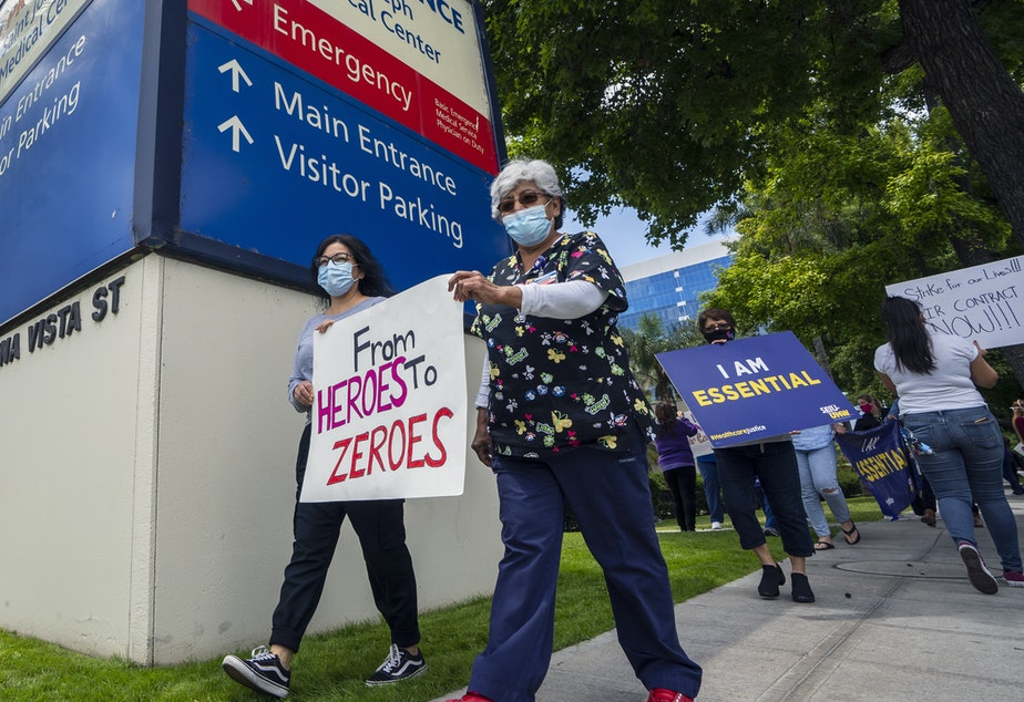 caption: Health care workers protest hospital understaffing and insufficient personal protective equipment last week outside Providence St. Joseph Medical Center in Burbank, Calif.