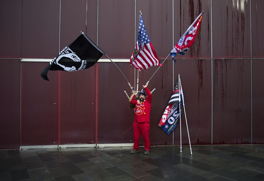 caption: Michael Thompson of Bellingham hoists a device for carrying flags onto his back on Sunday, January 5, 2020, during a 'United against Hate' rally organized by the 3% of Washington group outside of City Hall in Seattle.