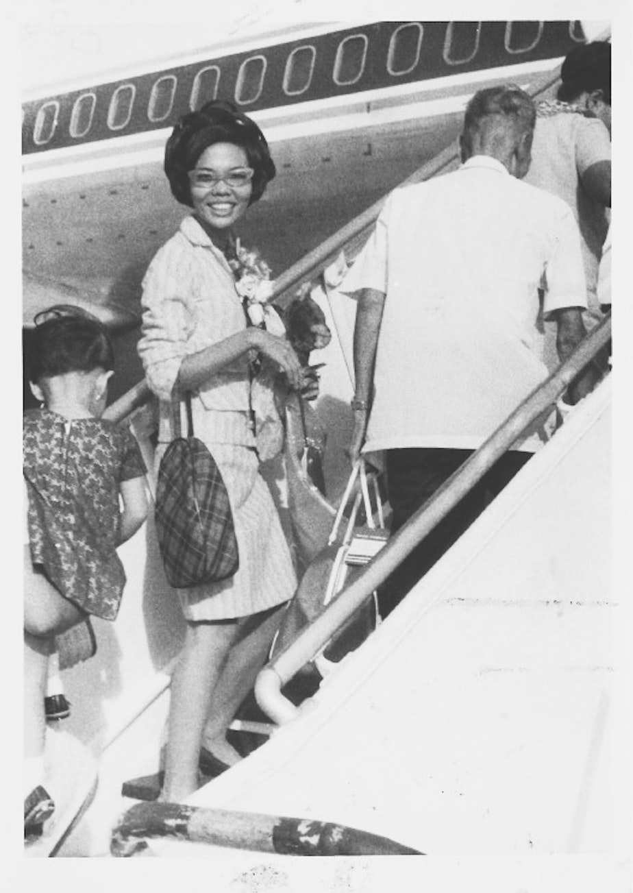 caption: Erlinda Conde boards the plane as she leaves her home in the Philippines for a new life in Chicago.