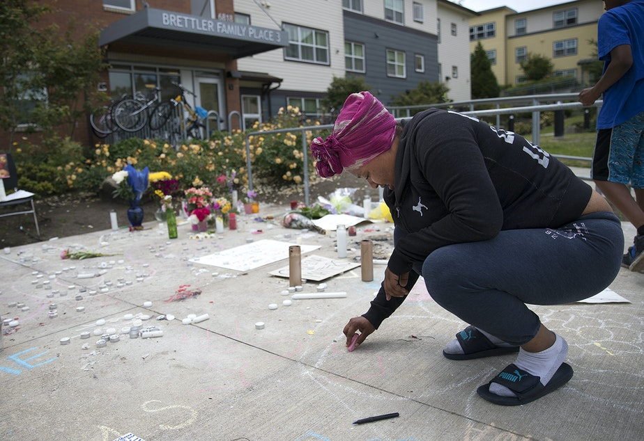 Alaina Williams, a friend and neighbor of Charleena Lyles, writes, 'Love U Leena,' in chalk at a memorial for Lyles on Monday.