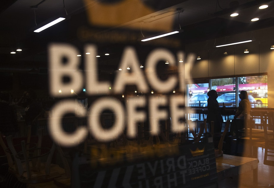 caption: The interior of Black Coffee Northwest is reflected in the front entrance of the business on Thursday, October 15, 2020, along Aurora Avenue North in Shoreline.