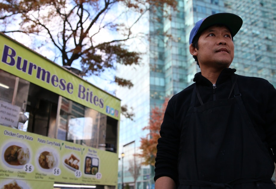 Myo Lin Thwey hopes he can make a good living selling Burmese food to Amazon workers on the street. Behind him: the Citibank tower in Long Island City. Eventually it will be filled with Amazon workers.