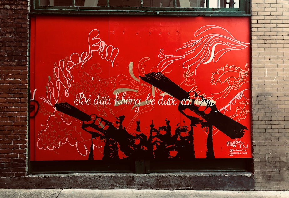"""caption: Seattle International District mural by Vietnamese artist Tân Nguyen and Black Seattle artist Moses Sun. The text reads, """"chopsticks in a bundle are unbreakable."""" This mural was part of the inspiration behind Kristin Leong's #AZNxBLM project. Learn more at RockPaperRadio.com."""