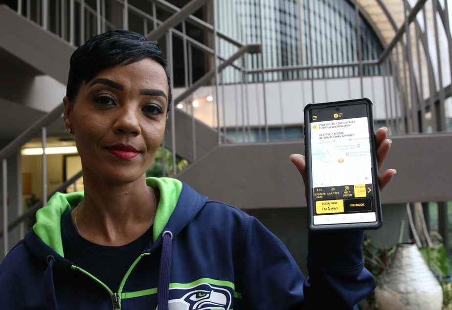 caption: Seattle Yellow Cab's Bershabet Yilma holds a phone with her company's app