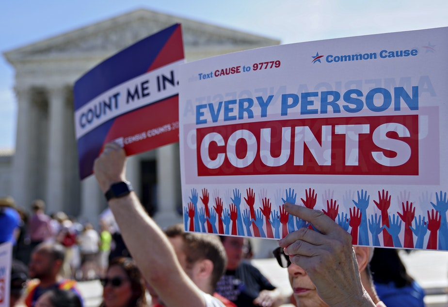 caption: Demonstrators hold signs about the 2020 census outside the U.S. Supreme Court in 2019.