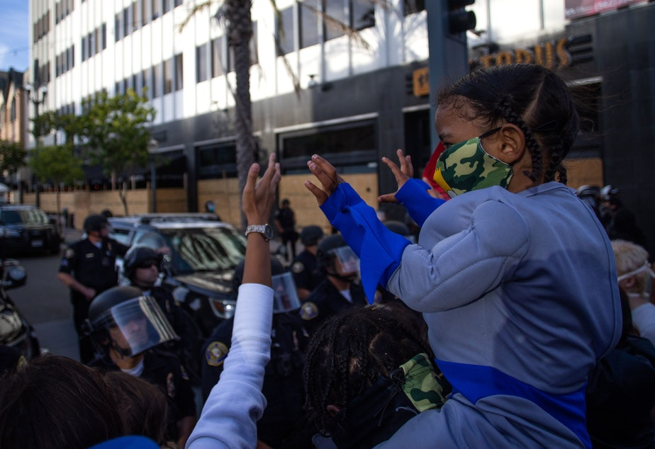 caption: A child holds up his hands in front of a row of police officers in downtown Long Beach on May 31, 2020 during a protest against the death of George Floyd, an unarmed black man who died while being arrested and pinned to the ground by the knee of a Minneapolis police officer. (APU GOMES/AFP via Getty Images)