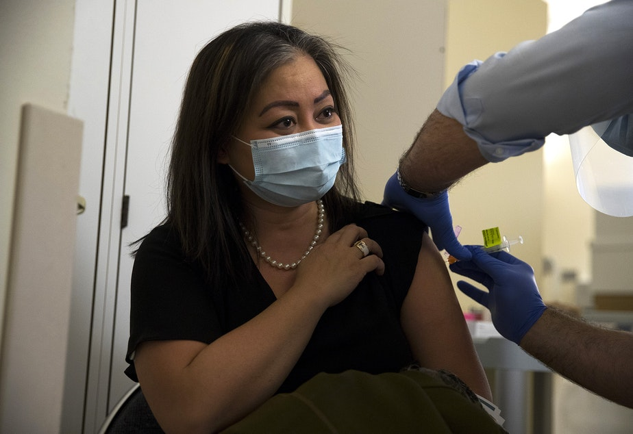 caption: Jennie Wu, Director of Urgent Clinics at Evergreen Health Medical Center, receives the first dose of the Moderna Covid-19 vaccine, administered by Dr. Ettore Palazzo on Wednesday, December 23, 2020, at Evergreen Health Medical Center in Kirkland.