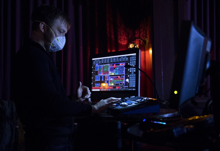 caption: Technical Director Michael Rotchadl wears a mask while working during a live-streamed Le Faux happy hour show on Wednesday, May 20, 2020, at Julia's on Broadway in Seattle.