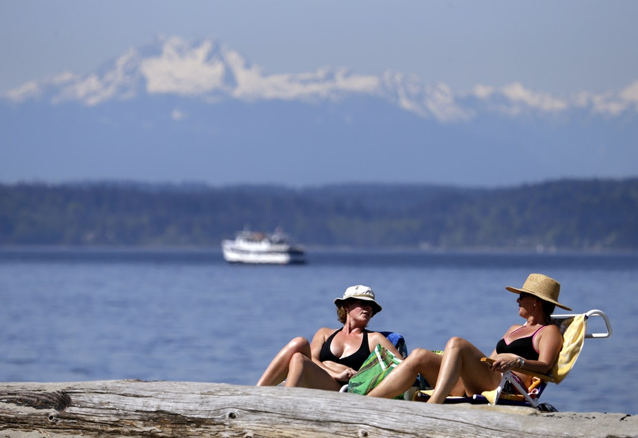 caption: Beach-goers in Seattle enjoy a Puget Sound shore in Seattle.