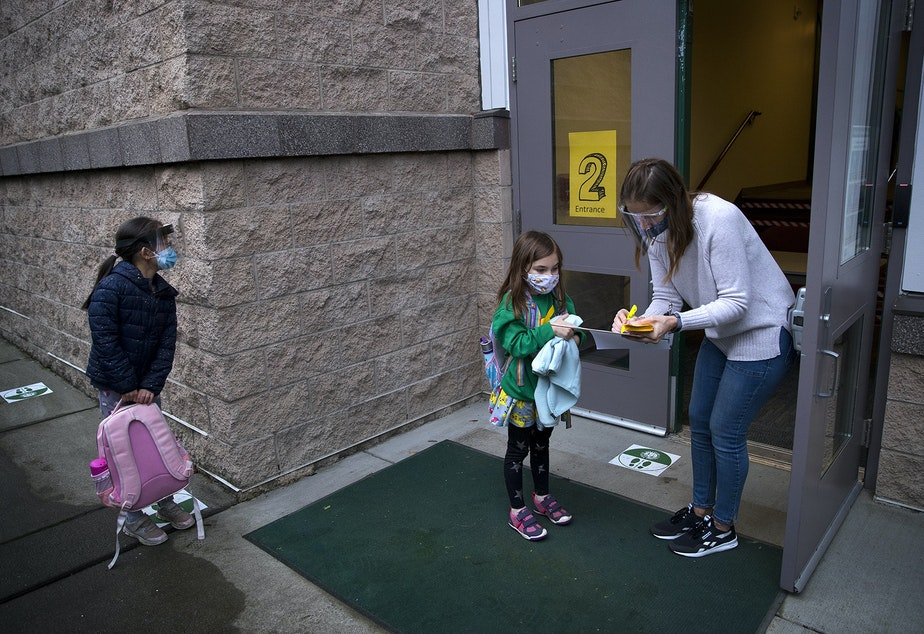 caption: General school assistant Vicki Premo, right, checks in second-grade student Cora on Thursday, January 21, 2021, as second-grade students returned to in-person learning at Somerset Elementary School in Bellevue.