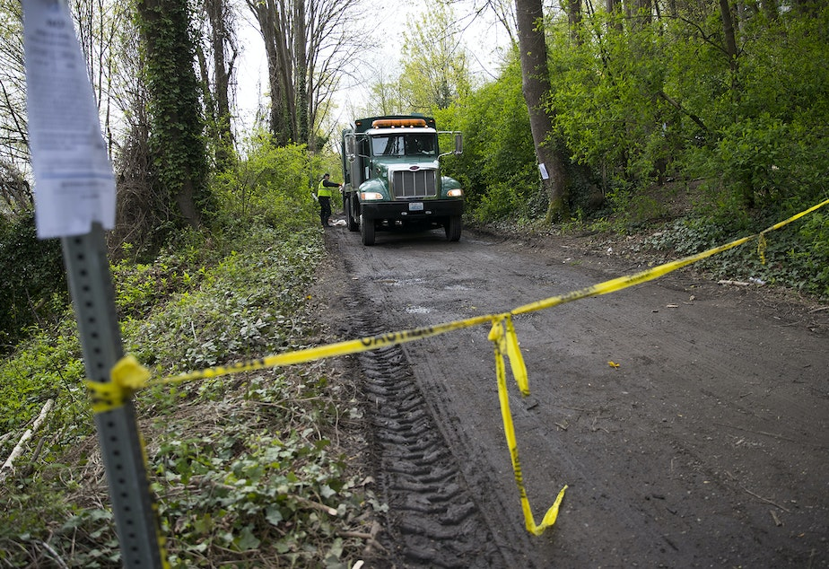 caption: A former encampment in Ravenna is roped off as crews clear out the area with a garbage truck on Wednesday, April 18, 2018, in Seattle.