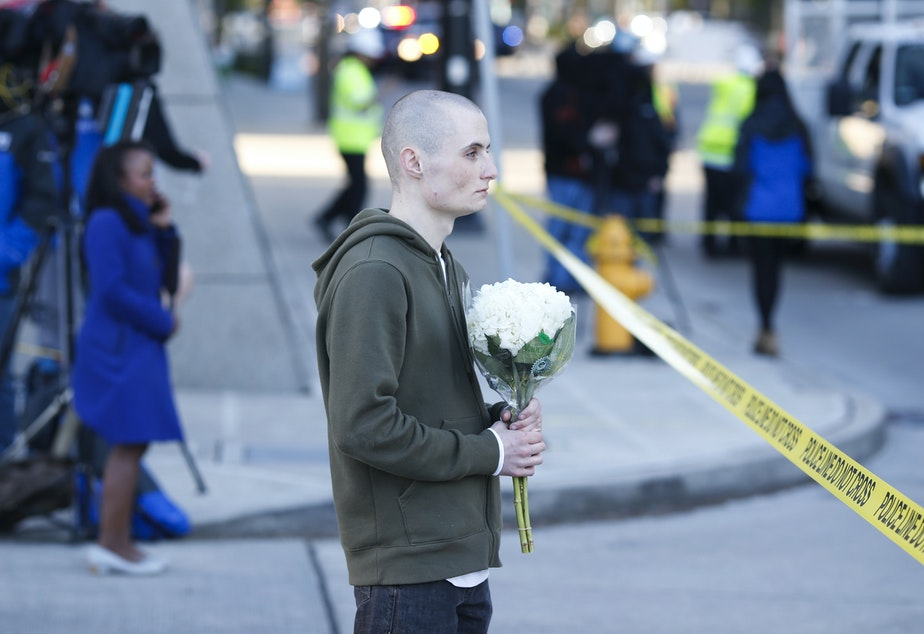 caption: Blake Haner, a Seattle resident, holds flowers for those who died at the scene of a construction crane collapse where several people were killed and several others injured Saturday, April 27, 2019, in the South Lake Union neighborhood of Seattle.