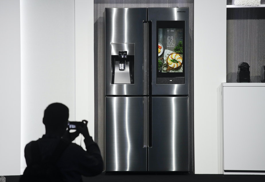 FILE- In this Jan. 8, 2018, file photo, an attendee takes pictures of the new Samsung Family Hub smart refrigerator during a news conference at CES International in Las Vegas. Payment networks and manufacturers are building payment functions into more devices. Samsung's Family Hub refrigerator lets users order groceries from the Groceries by Mastercard app.