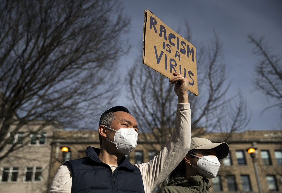 caption: Michael Lee holds a sign in the air that reads 'Racism Is a Virus,' as hundreds gathered for the 'We Are Not Silent' rally and march against the rise in racist violence toward both Asian American and Pacific Islander communities at Hing Hay Park in Seattle's Chinatown-International District.