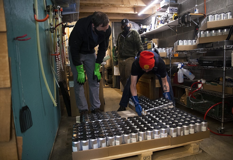 caption: From left, Chris Smith, Scott Jones and John Marti, right, arrange boxes of canned beer from a mobile canning unit onto a pallet on Friday, May 22, 2020, at Lowercase Brewing in Seattle.
