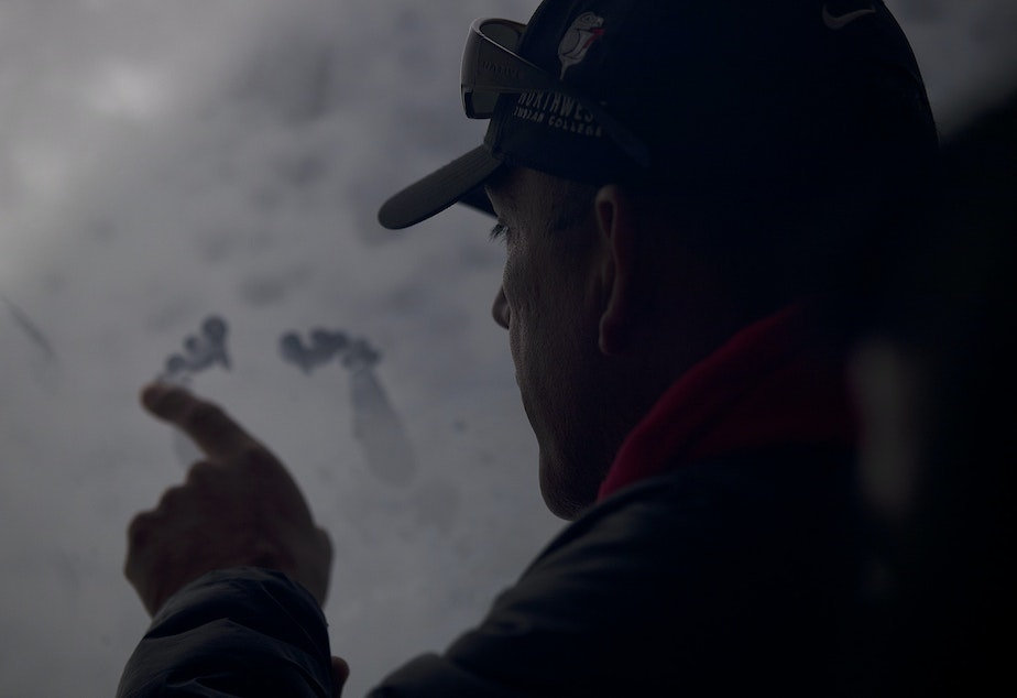 Lummi Tribal Chairman Jay Julius uses the side of his fist and finger to make what looks like feet on the inside of a window aboard King County Research Vessel SoundGuardian on Wednesday, April 10, 2019, in the waters west of Bellingham.