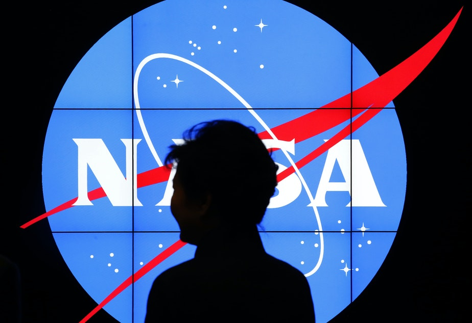 South Korean President Park Geun-hye walks past a NASA logo during a tour at the agency's Goddard Space Flight Center in Greenbelt, Md.