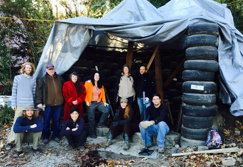 caption: Roxanne Fonder Reeve (red jacket) stands with volunteers from Earthship Seattle in front of their trash studio in progress.