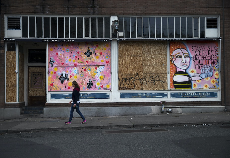 caption: Leslie Buker walks by Oddfellows Cafe + Bar, with a mural painted by Stacy Milrany displayed, on Sunday, March 22, 2020, on 10th Avenue in Seattle.