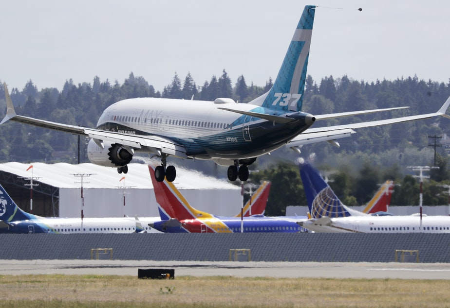 caption: A Boeing 737 Max heads to a landing past grounded 737 Max aircraft at Boeing Field following a test flight Monday in Seattle. The jet took off from Boeing Field earlier in the day, the start of three days of re-certification test flights that mark a step toward returning the aircraft to passenger service.