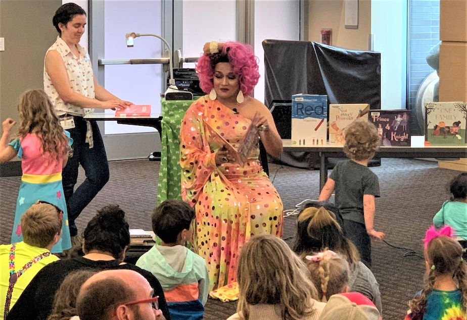 A drag performer reads to families at a King County Library System Drag Queen Story Hour.